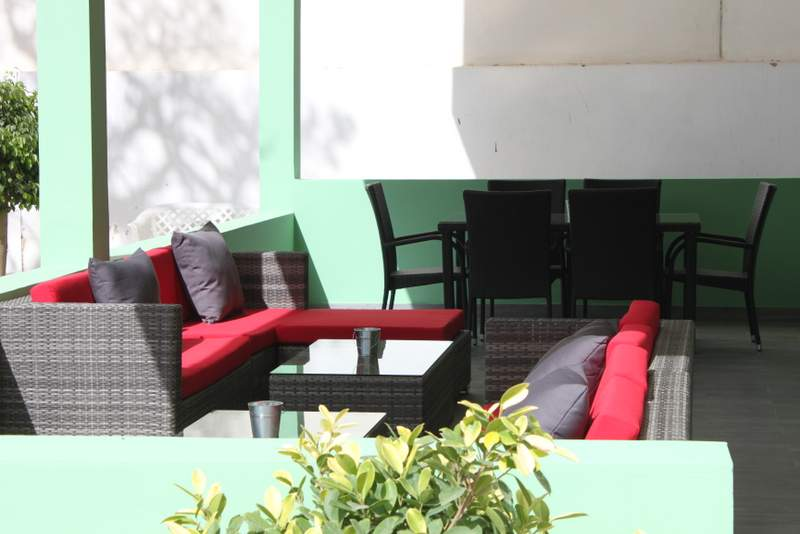 Hello, seafoam green walls, black and grey woven outdoor couches with red cushions, and an outdoor table for six!