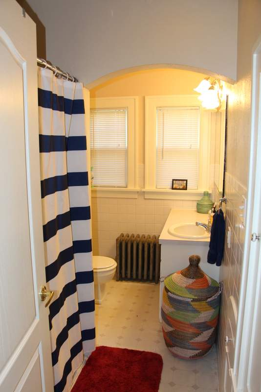 The bathroom, featuring stripes and more baskets.