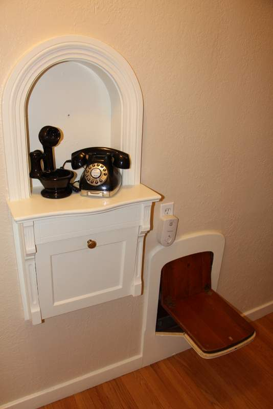 A unique feature: a fold-down phone chair. Old homes are so cute.